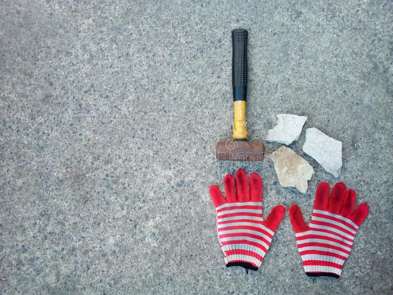 Hammer and glove on cement royalty free stock image