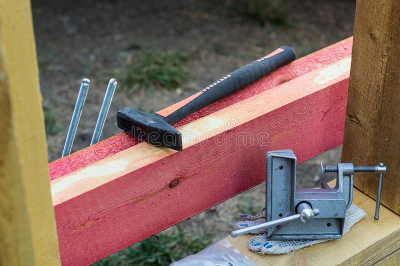 Hammer and hand screw clamp on background of the construction. House metal architect carpenter labor timber tool wood woodwork working man workshop bricolage stock images
