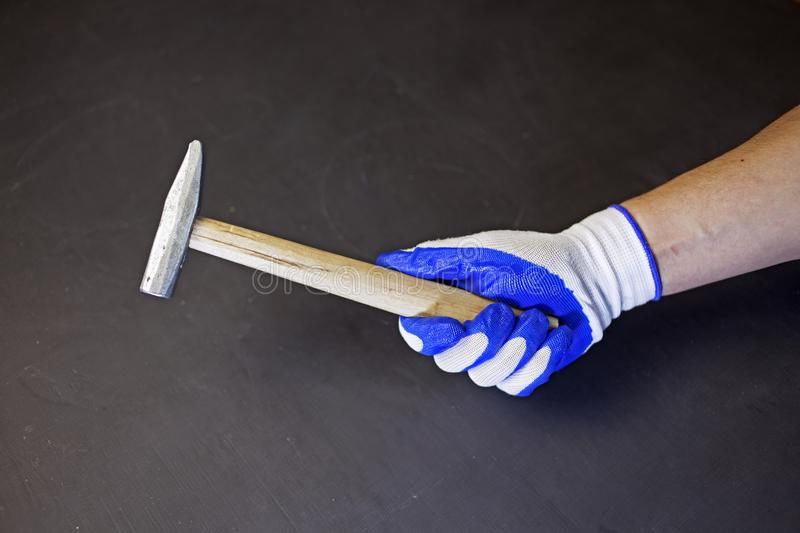 Hammer in the hands of the worker in protective gloves stock photography