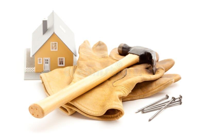 Hammer, Handschuhe, Nägel und Haus stockfotos