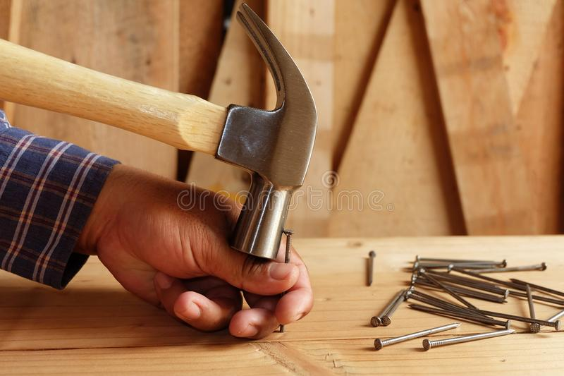 Hammer hitting the finger Do not hit nails. And a pile of wood background stock image