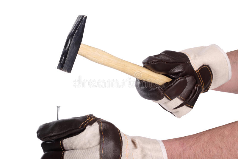 Hammer III. Hammer in working hands with glove hitting a nail royalty free stock photo