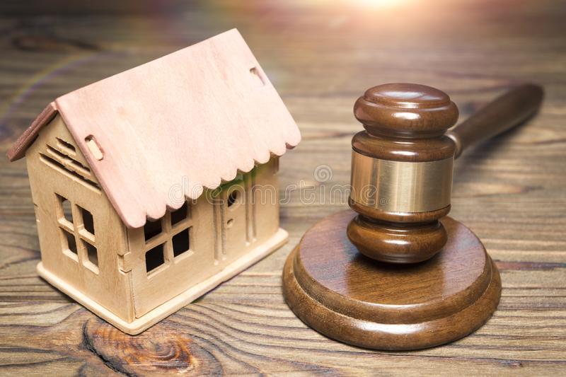 Hammer of a judge, breadboard model of a wooden house. Against the background of a wooden table. seizure of property. housing law royalty free stock photography
