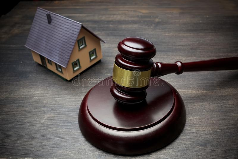Hammer of the judge, the house on a black wooden background. real estate. royalty free stock images