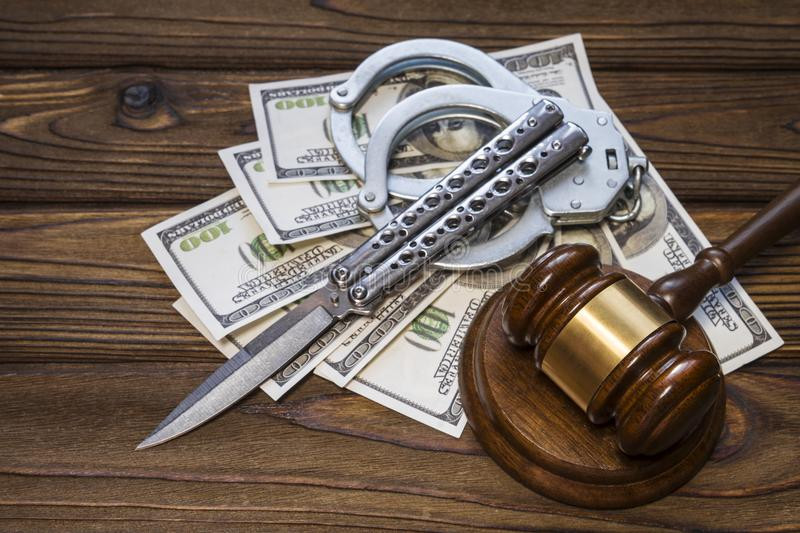 Hammer of a judge; knife; handcuffs and money dollars on a wood texture background. Idea: Justice; crime and punishment; court; law. armed robbery; rebel stock photography