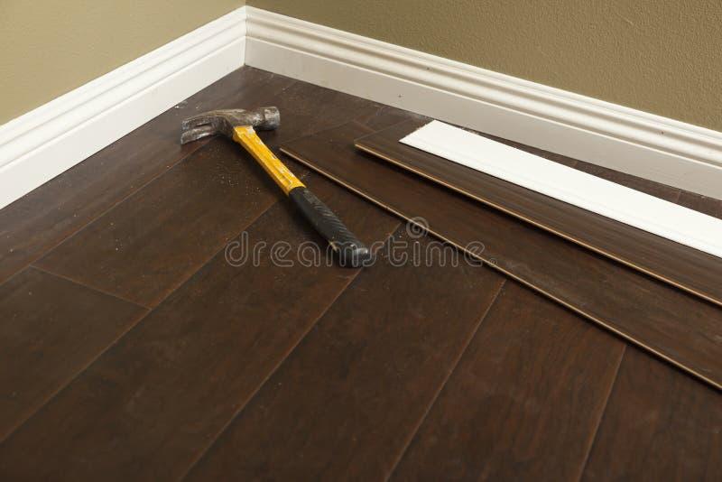 Hammer, Laminate Flooring and New Baseboard Molding. Abstract stock image