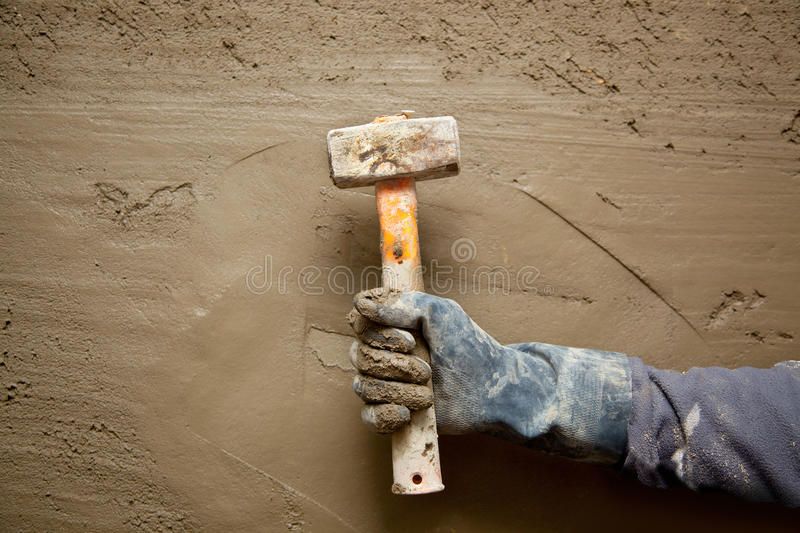 Hammer man with gloves in grunge cement background. Hammer man hand with gloves in grunge cement mortar background royalty free stock images