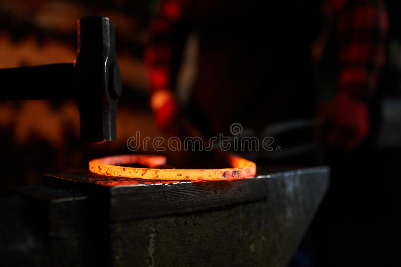 Hammer and molten metal. Hammer over hot molten metal workpiece on anvil with blacksmith on background stock image