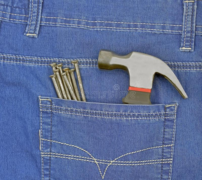Hammer and nails in blue jeans pocket royalty free stock photography