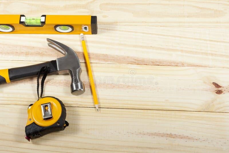 Hammer, Niveau und Maßband, die auf einen wodden Hintergrund legen stockfotografie
