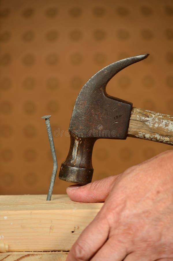 Hammer Smashing Man's Thumb. At woodworkers shop stock photo