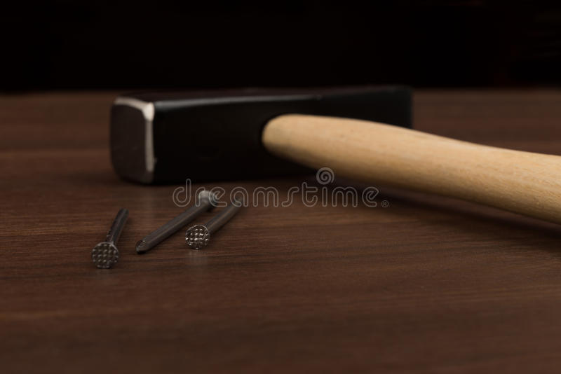 Hammer and three nails on table stock images
