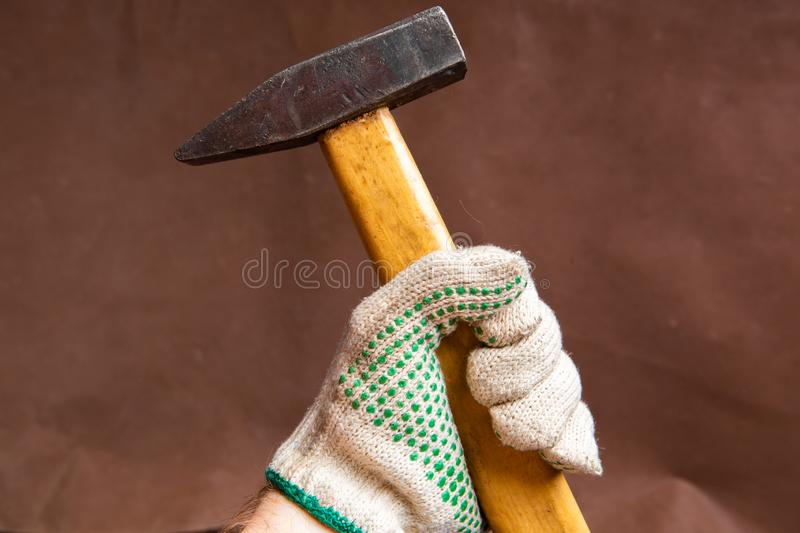 hammer tool in hand wearing glove prepaire to hit closeup stock image