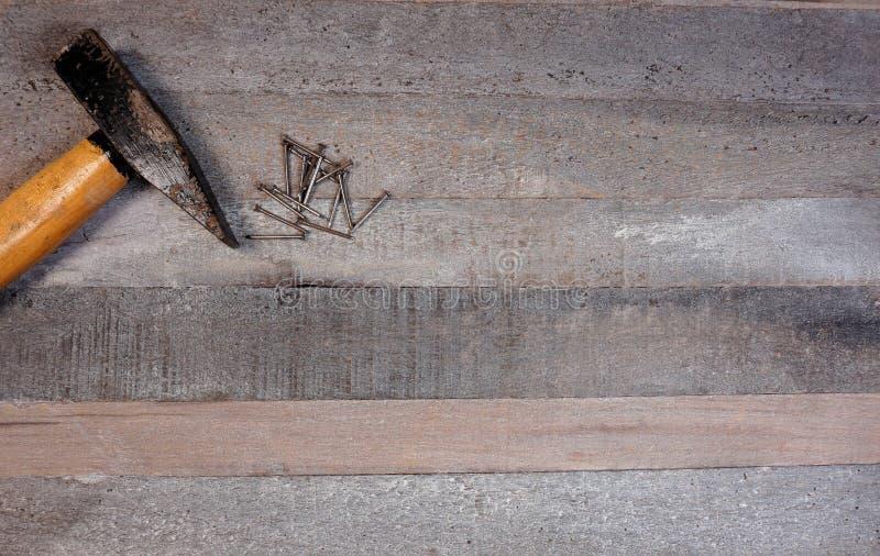 Hammer und Nägel auf einem hölzernen Bretthintergrund stockbild