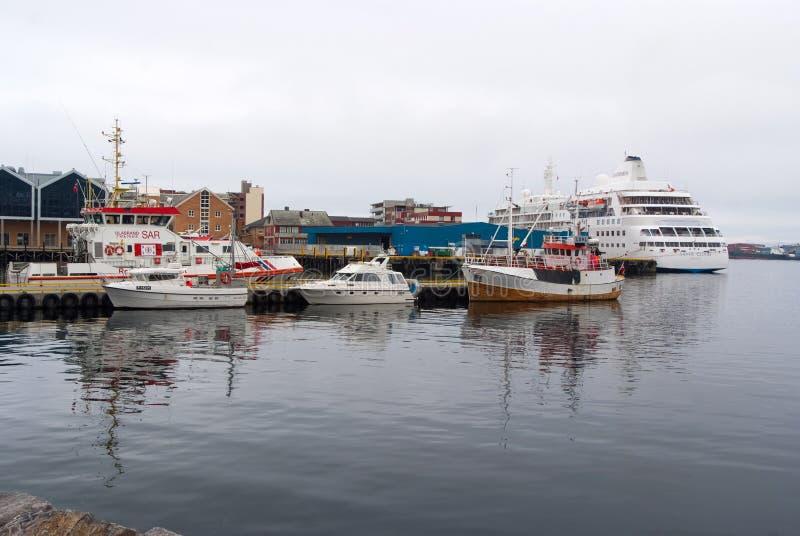 Hammerfest, Noorwegen - Januari 21, 2010: schepen en boten in overzees dok op grijze hemel Watervervoer en vervoer stock fotografie