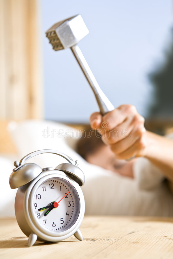 Hammering. Close up view of big kitchen hammer is ready to crash alarm-clock royalty free stock photo
