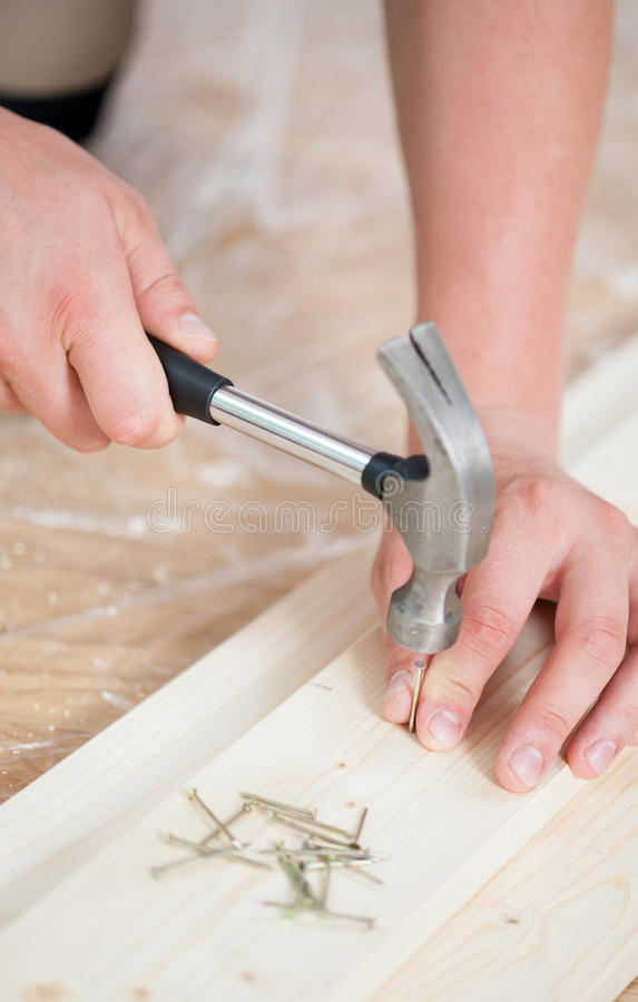 Hammering nails into wooden board royalty free stock photo