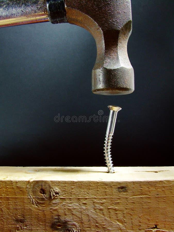 Hammern einer Schraube stockbilder