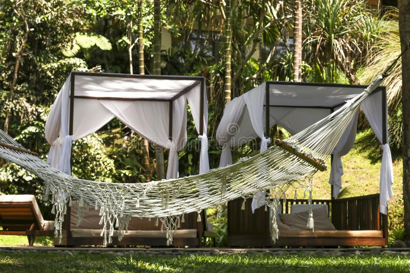 Hammock on the background of cozy gazebos, a place of rest and relaxation in a beautiful tropical garden in Bali island, Indonesia stock photo