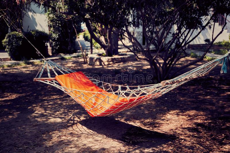 Hammock in the backyard. Under the shadows of the trees royalty free stock images