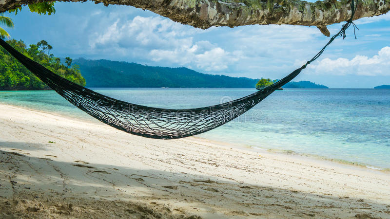 Hammock on the Beach, Batu Lima, Coral Reef of an Homestay Gam Island, West Papuan, Raja Ampat, Indonesia.  stock photos