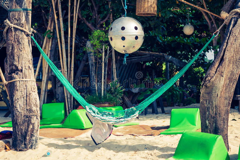 Hammock hanging under exotic tree on beach with white sand below royalty free stock photography