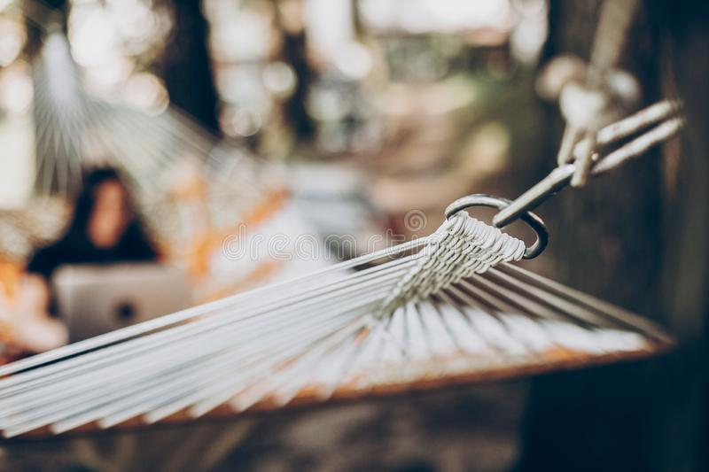 Hammock hook close-up, relaxation concept, woman with laptop in the background stock image