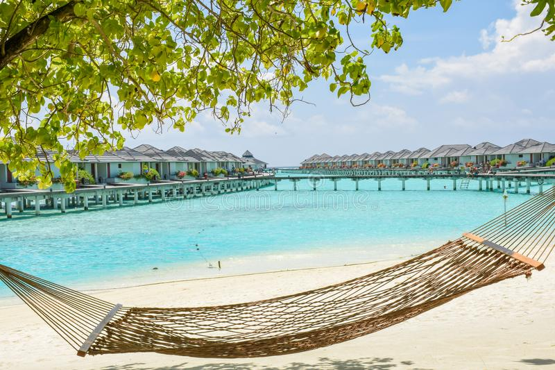 Hammock at the tropical beach with over water villas at resort stock photo