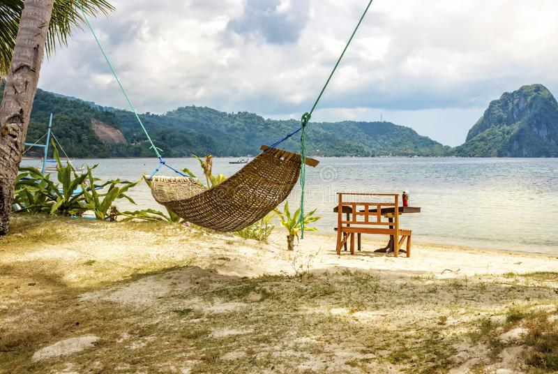 A hammock between two palm trees on the beach. Beautiful beach. The concept of rest and recreation. Beautiful tropical island. royalty free stock photo