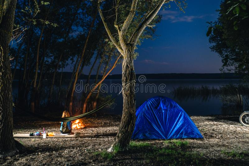 Hammok and girl is sitting near bonfire. Blue Camping Tent Illuminated Inside. Night Hours Campsite. Recreation and Outdoor. Lake. Hiking, vacation, active stock photography