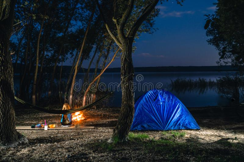 Hammok and girl is sitting near bonfire. Blue Camping Tent Illuminated Inside. Night Hours Campsite. Recreation and Outdoor. Lake. Hiking, vacation, active stock photo