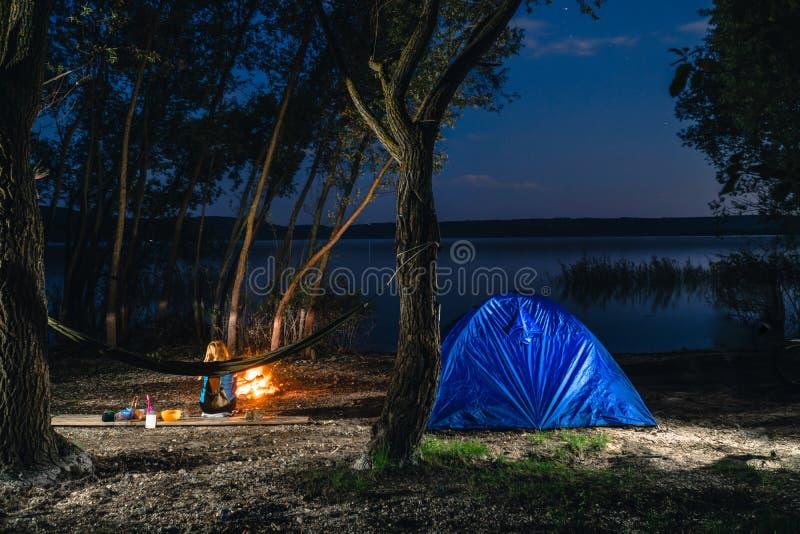 Hammok und M?dchen sitzt nahe Feuer Blaues Campingzelt nach innen belichtet Nachtstunden-Campingplatz Erholung und im Freien See stockfoto