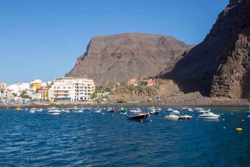 Hamnen av Vueltas i Valle Gran Rey med fartyg, byggnader och berg royaltyfri fotografi