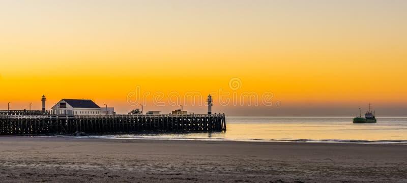 Hamnpir på stranden av blankenberge, Belgien, en fartygsegling i havet, den härliga solnedgången och den färgrika himlen arkivfoto