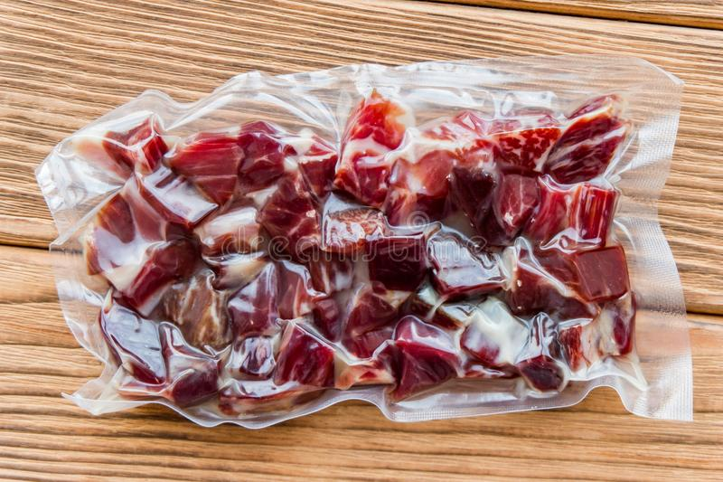Hamon diced in vacuum-packed. Jamon. Wooden background royalty free stock photography