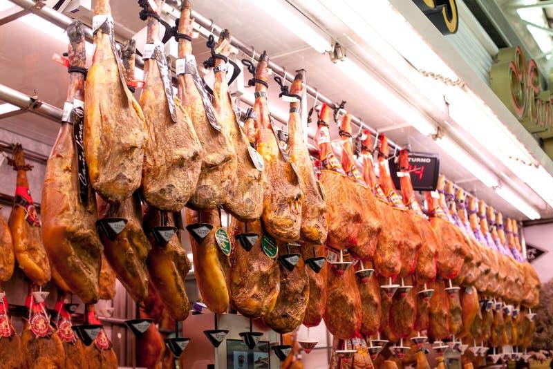 Hamon espanhol no mercado de Valência, iberico do jamon na carne de porco isolada, carne nacional tradicional do pé do preto da v foto de stock