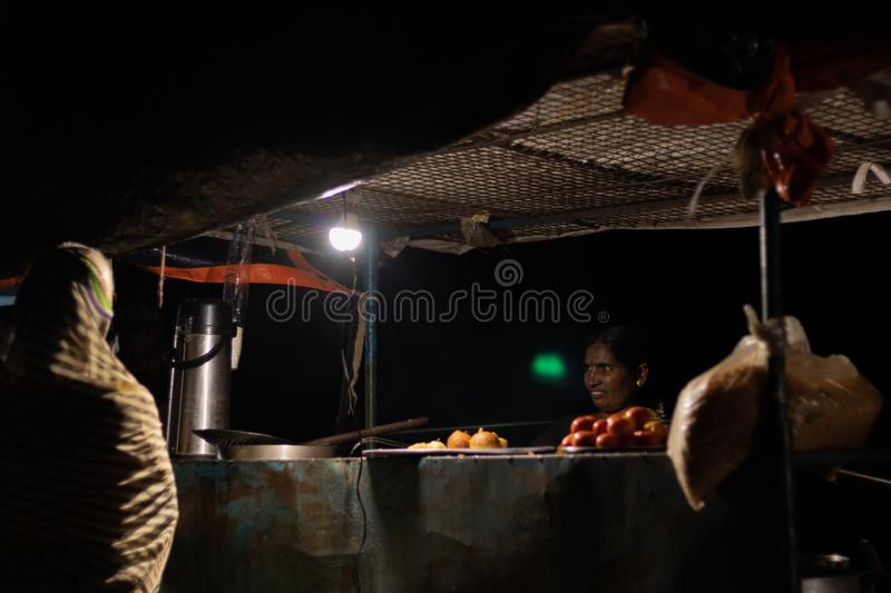 Hampi, India July 8, 2019 : Indian night strret food, Woman selling snacks at street food carts royalty free stock images