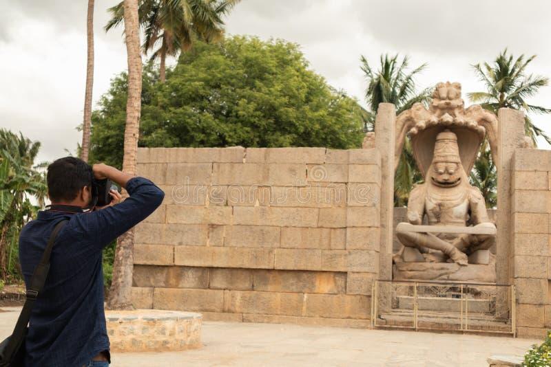 Hampi, India 9 luglio 2019: Prova turistica al catpure Ugra Narsimha o Lakshmi Narsimha a Hampi L'avatar del uomo-leone di signor fotografie stock