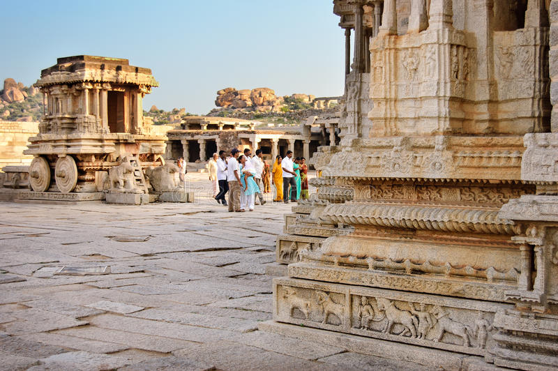 Hampi, India - 19 November 2014: People walking in front of stone chariot in courtyard of Vittala Temple in Hamp royalty free stock photo