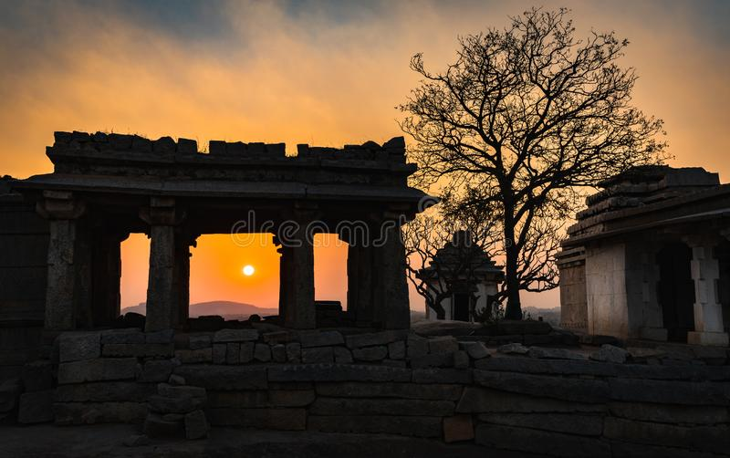 Hampi karnakata india temple and silhouette tree at sunset point colorful sky and. Hampi karnakata india temple and silhouette tree at sunset point colorful sky stock photography