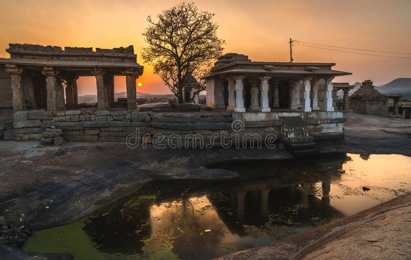 Hampi karnakata india temple and silhouette tree at sunset point colorful sky and reflection. In a little lake royalty free stock photo