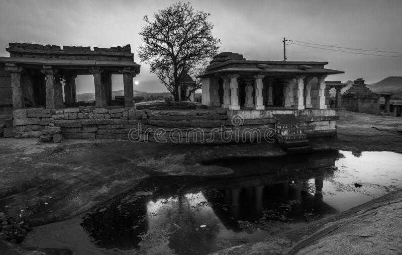Hampi karnakata india temple and silhouette tree at sunset point reflection in a little lake. Black and white stock image