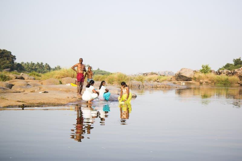HAMPI, KARNATAKA, INDIA - 19 Februari 2013 - Gelukkige Indische mensen bij de rivier kleedde kleurrijk waskleren stock foto's