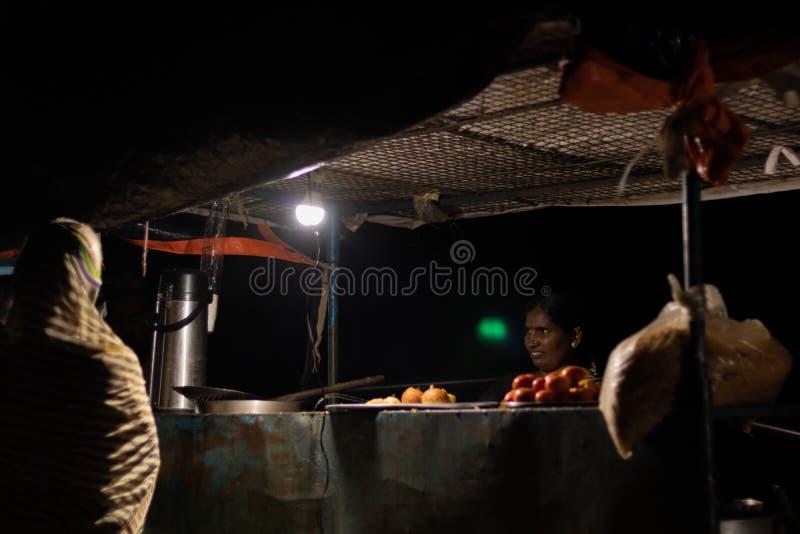 Hampi, la India 8 de julio de 2019: Comida india del strret de la noche, mujer que vende los bocados en los carros de la comida d imágenes de archivo libres de regalías