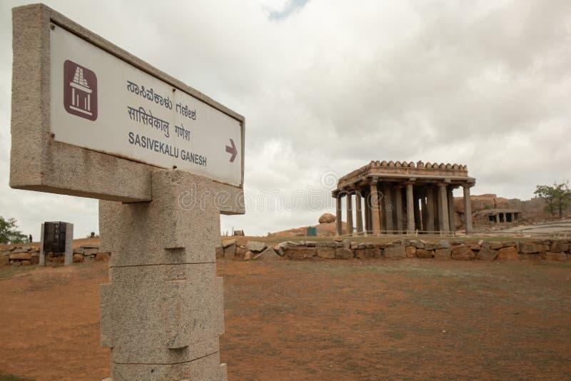 Hampi, la India 8 de julio de 2019: dirección de la demostración del tablero de la señalización al monumento de Sasivekalu Ganesh imagen de archivo libre de regalías