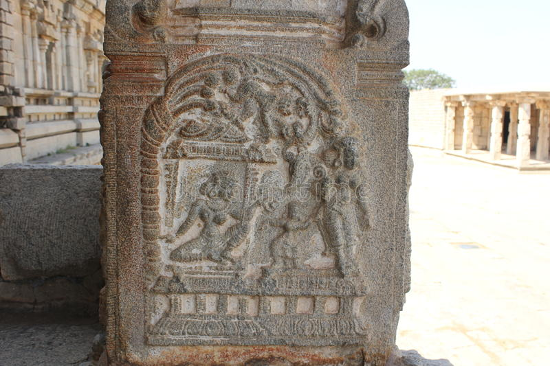 Hampi Vittala Temple pillar carving of hanuman meeting sita or human guarded by demon, monkey watching from tree top. This stone pillar carving shows hanuman royalty free stock image