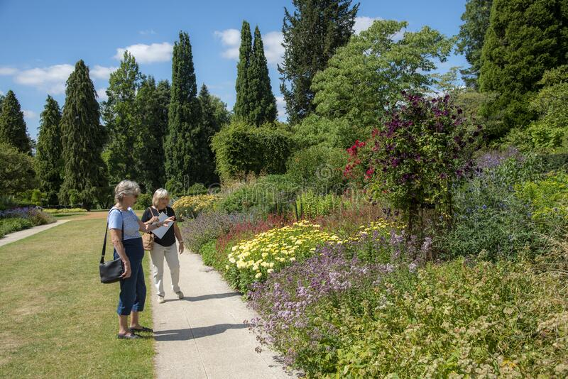 Tourists admire the plants and flowers in a formal garden in Hampshire. royalty free stock image