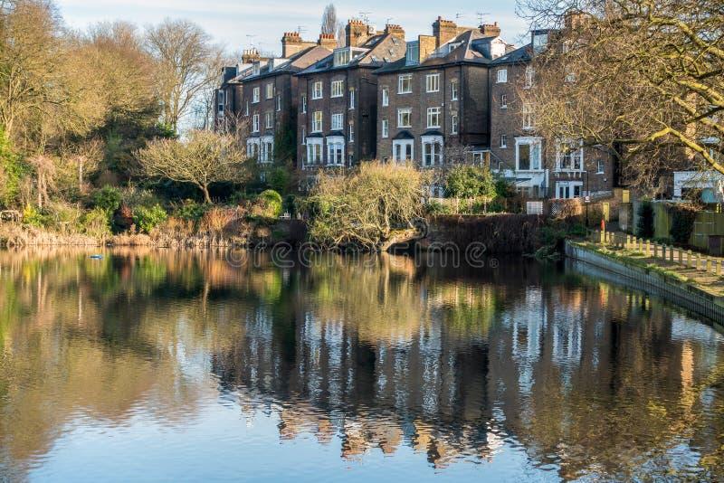 HAMPSTEAD LONDON/UK - DECEMBER 27: Rad av hus vid en sjö på royaltyfri fotografi