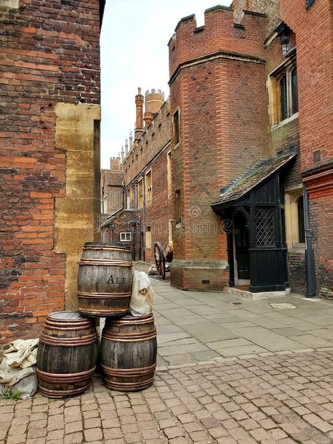 Hampton Court Palace rustic alley with ale barrels royalty free stock images