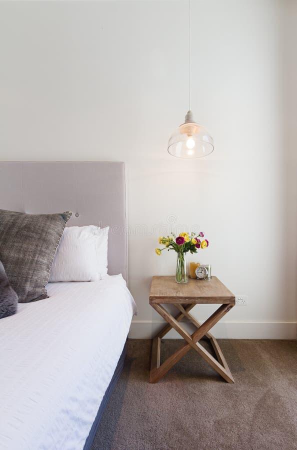 Hamptons redete Nachttisch mit dem Hängen des hängenden Lichtes im luxu an stockbild
